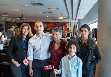 immigrants: TORONTO,CANADA-AUGU ST 27,2014: Hispanic family becomes Canadian citizens.Canadian nationality law determines who is granted to. A permanent resident who lived in Canada a period of time is an example