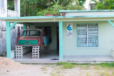 private parts: SANTA CLARA,CUBA-JUNE 28,2014: Private house keeping a 1974 Peugeot 404 body either for selling it or putting together the car. A car is a valuable since it may be a significant source of income.