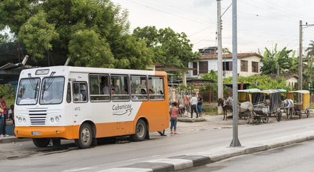 despacio: SANTA CLARA, CUBA 28 DE JUNIO DE 2014: El gobierno de Raúl Castro ha comenzado a colocar estatal ómnibus urbano que ahora compite con los coches de caballos que son privados.