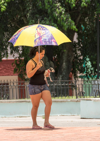all weather: SANTA CLARA,CUBA-AUGUST 17,2014: Cuba temperature has risen in about 4 degree in the last 8 years, government has educated people to protect with umbrellas and avoid skin cancer.