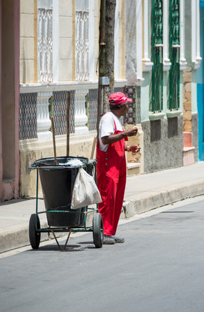 scorching: SANTA CLARA,CUBA-AUGUST 17,2014: Street sweeper taking a break in his route during a scorching heat day. The sweepers are now privately owned cooperatives hired by the government.