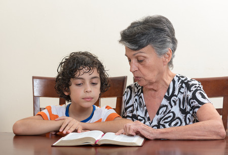 Grandmother teaching the Holy Bible to her grandson.  photo