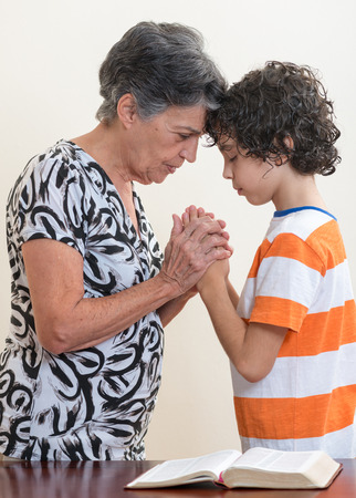 niño orando: Abuela y nieto orando juntos en su devocional cristiana diaria. Foto de archivo