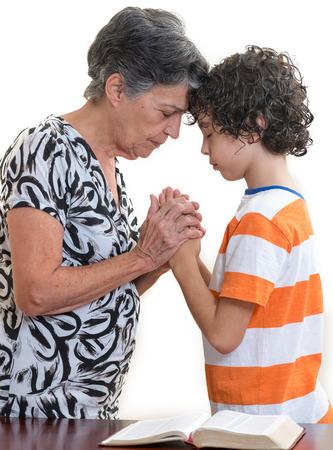 familia orando: Abuela y nieto orando juntos en su devocional cristiana diaria. Foto de archivo