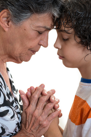 Grandmother and grandson praying together in their daily Christian devotional.  photo