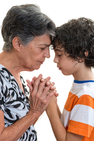 praying together: Grandmother and grandson praying together in their daily Christian devotional.