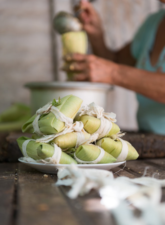 Woman making tamales in Cuba, the tamal  is a traditional Mesoamerican dish made of masa photo