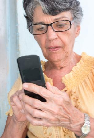 Senior woman using digital technology or mobile phone photo