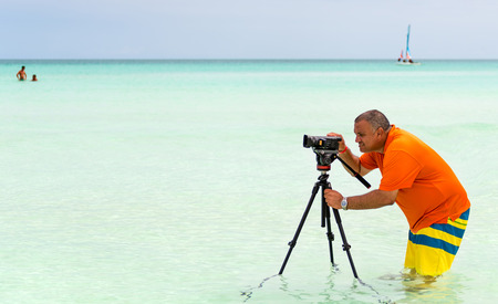 Photographer looking for a different angle and shooting from inside the beach water photo