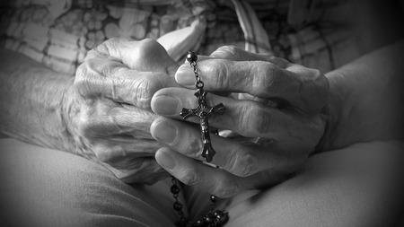 alabando a dios: Mujer mayor que sostiene un rosario en sus viejas manos, mientras rezaba, devocional diario cristiano del creyente femenina cat�lica alabando a Dios en el Cielo