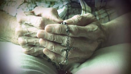 Senior womans hand holding a rosary or crucifix while praying, Christian daily devotional of a faithful catholic woman
