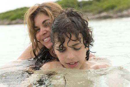 madre soltera: Madre soltera con su hijo disfrutando de una playa tropical con agua clara