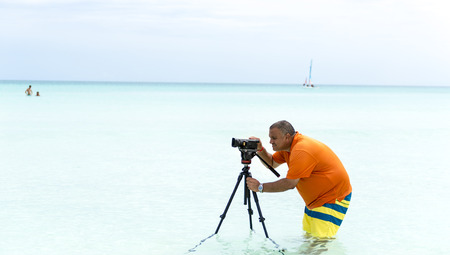 Videographer takes images of a beautiful tropical beach from inside the water photo