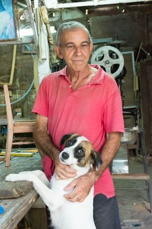 impoverish: Retired Cuban carpenter,nowadays self employed at home with his own homemade carpentry taking a break and petting his dog.