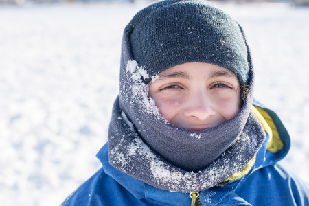 frigid: Close up of innocent expression of a child playing in the white snow during the  frigid Canadian Winter