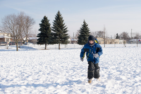 frigid: Child boy running in an open field of snow during a frigid Canadian Winter