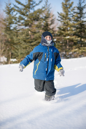 Child boy running and having fun in the fresh white snow during a frigid day in the Canadian Winter Stock Photo
