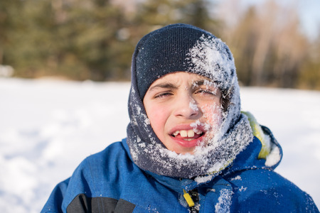 frigid: Canadian child boy playing and enjoying the fresh white snow in a frigid day during Winter in Toronto Stock Photo