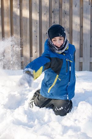 having fun in the snow: Canadian child boy throwing snow and having fun with the simple free things in life during a frigid day in the Winter