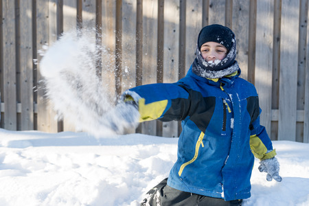 frigid: Child boy throwing snow balls, having fun with the simple things in life and enjoying the frigid Canadian Winter Stock Photo