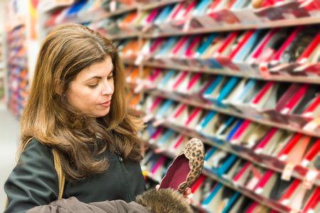 buying shoes: Edad Media, la mujer de la vida real de comprar zapatos en una tienda de zapatos Foto de archivo