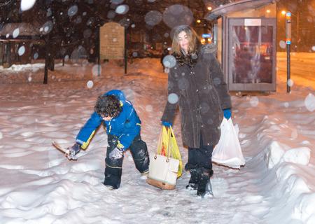 madre soltera: La vida cotidiana de una madre soltera en Toronto durante el invierno, despu�s del trabajo que recoge su ni�o, compra de comestibles y volver a casa bajo una nevada