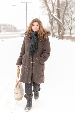 frigid: Beautiful middle age woman walking in the city sidewalk during a snowfall on a frigid day in the Canadian Winter Stock Photo