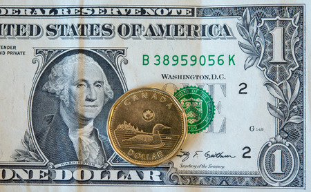 us dollars: The Canadian dollar or loonie is under pressure amid weak oil prices and a strengthening U.S. currency.  Today, the loonie dropped to 78.39 cents for a U.S dollar the lowest in a many years. Stock Photo