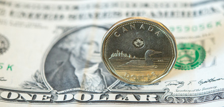 canadian coin: The Canadian dollar or loonie is under pressure amid weak oil prices and a strengthening U.S. currency.  Today, the loonie dropped to 78.39 cents for a U.S dollar the lowest in a many years. Stock Photo