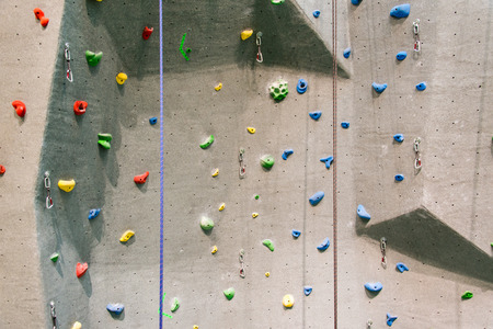 recreational climbing: Indoor rock climbing wall in a sport facility where many practice to be fit and in better health Stock Photo
