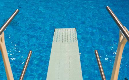 オリンピック スポーツ ダイビング屋内スイミング プールで明確な透明な青い水トランポリンからの眺め 写真素材