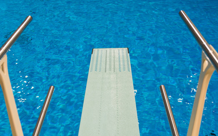 View from a trampoline in an sports competition sport diving indoor swimming pool with clear transparent blue water