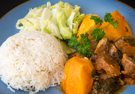 the lamb: Cuban Cuisine: lamb stew in tomato sauce with potatoes,white rice and salad as side plates