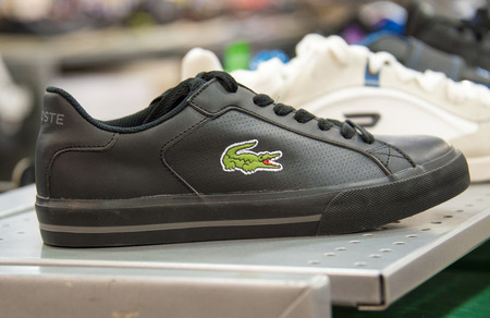 shoe shelf: Lacoste Shoe in store shelf, Lacoste is a French clothing company founded in 1933 that sells high-end clothing, footwear, perfume, leather goods, watches, eyewear, and most famously polo shirts.
