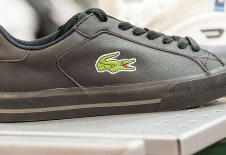 shoe shelf: Lacoste Shoe in a store shelf; Lacoste is a French clothing company founded in 1933 that sells high-end clothing, footwear, perfume, leather goods, watches, eyewear, and most famously polo shirts. Stock Photo