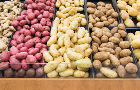 grocery: Different varieties of potatoes in a shelf in a grocery store