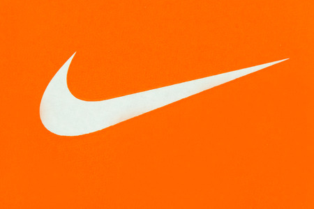logo marketing: White Nike Logo on Orange Background;Nike, Inc. is an American multinational corporation that is engaged in the design, development, manufacturing and worldwide marketing and sales of footwear, apparel, equipment, accessories and services Stock Photo
