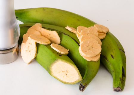 starchy food: Cuban Cuisine: Delicious green plantain bananas over white background not isolated along with chips or fries and a fruit with a transversal cut.