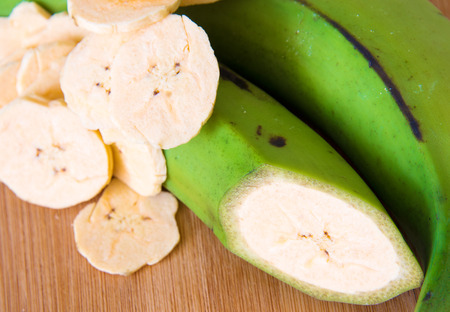 Cuban Cuisine: Delicious green plantain bananas over wood cutting board along with chips or fries and a fruit with a transversal cut.