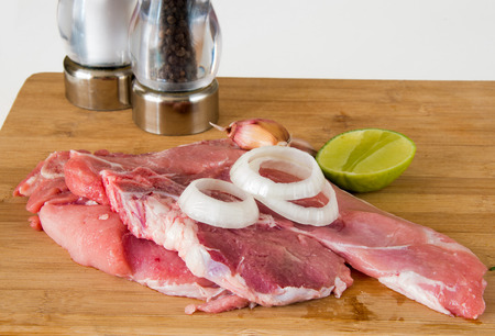creole: Cuban Cuisine: Raw pork meat steaks in cutting board with traditional and creole elements like lime,garlic,onion,salt and pepper