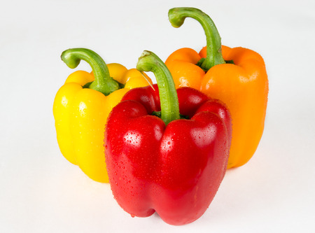 Multicolor bell pepper produce with water droplets for freshness over a white background. photo