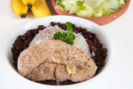 creole: Traditional Creole Cuban Cuisine: pork steak, white rice,and black beans over white background. Stock Photo