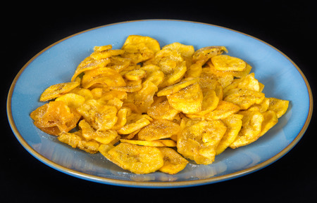 creole: Cuban Cuisine: delicious green plantain salty chips or fries served for snack in a blue plate. Green plantain chips or fries are part of the Cuban traditional and creole cuisine Stock Photo