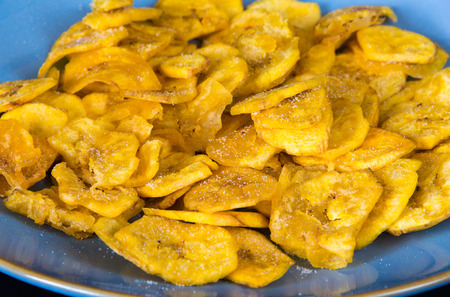 Cuban Cuisine: delicious green plantain salty chips or fries served for snack in a blue plate. Green plantain chips or fries are part of the Cuban traditional and creole cuisine 스톡 콘텐츠