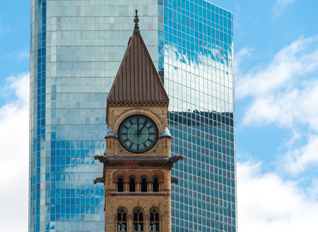 variance: Architectural contrast: Old City Hall with a glass wall of a modern building as a background. Building was designed by Edward James Lennox in a variance of the Romanesque revival architecture called Richardsonian Revival.  The building is located at the c Stock Photo