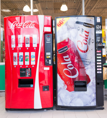 despite: TORONTO,CANADA-APRIL 4,2015: Coca Cola and a generic brand name machines in grocery store. Despite unhealthy reviews carbonated drinks sell a lot and many companies want a cut in profits Editorial