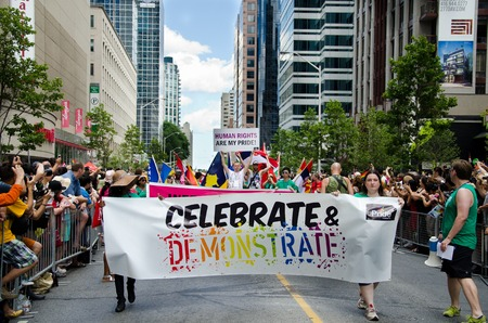marchers: Marchers with flags and banners at pride parade in Toronto pass through the street as crowds of spectators cheer from the sidelines