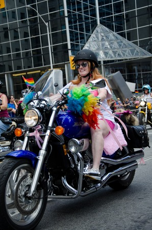 onlooker: Woman biker at pride parade Toronto riding a blue motorbike in a group decorated with rainbow colors and sporting helmet and sunglasses