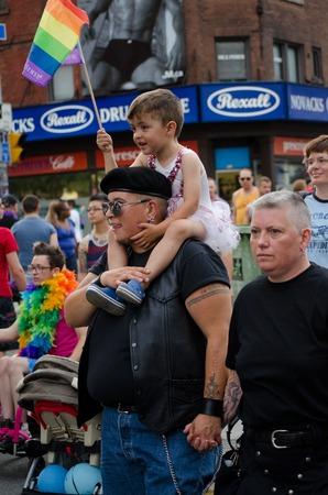 transexual: Pareja con ni�o en el hombro en el desfile del orgullo en Toronto ni�o lleva un tut� blanco y agitando una bandera del arco iris en un contexto de construcci�n de la se�alizaci�n y la gente.