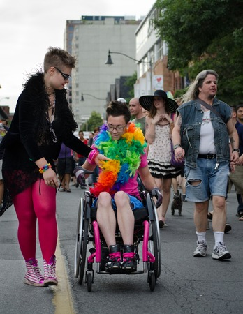 onlooker: Wheelchair enabled participant in pride parade Toronto wearing glasses and sporting a rainbow feather scarf going down the street with other marchers